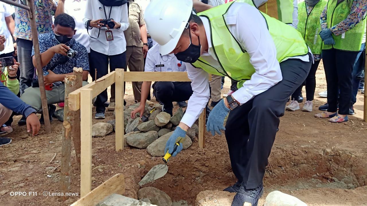 Tampak Bupati Iskandar Kamaru melakukan peletakan batu pertama Rumah Nelayan di Desa Tabilaa